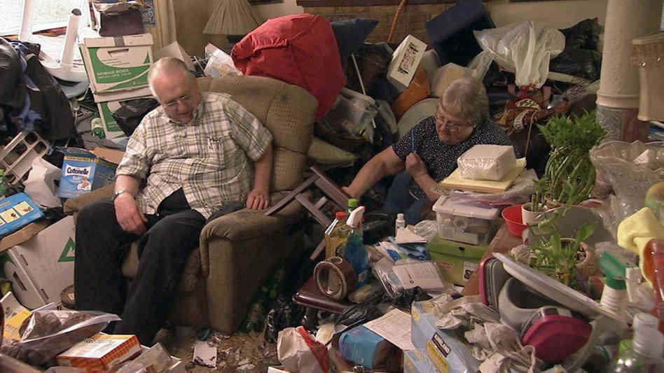 Photo of old couple sitting in a mess